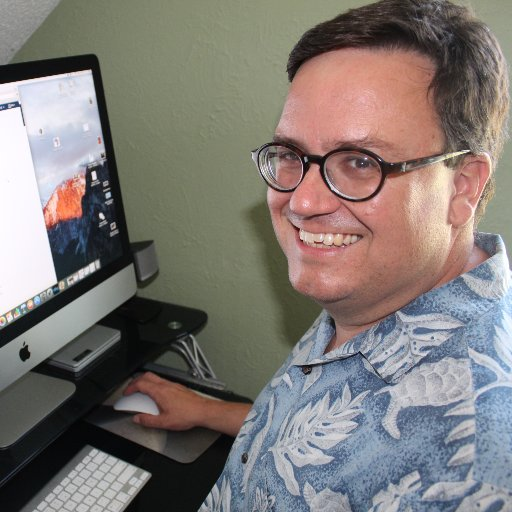 Middle-aged white man sitting at a computer.